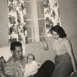 This black and white photograph from March 1958 includes two young adults and one infant. The male adult holds the infant, his niece and goddaughter; the female sits to the right, gazing on the infant who is her new goddaughter